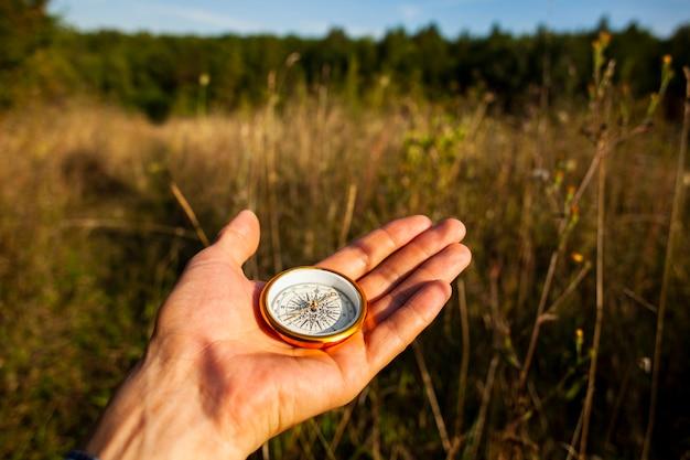 Kompas trzymany ręcznie i niewyraźne tło