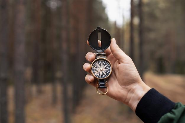 Kompas w dłoni człowieka na tle lasu