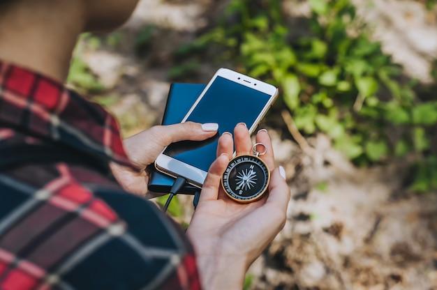 Kompas w dłoni dziewczyny ze smartfonem i powerbankiem. na tle trawy i piasku.