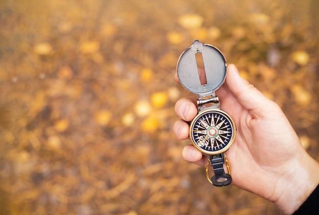Kompas w ręce mężczyzny na tle liści jesienią