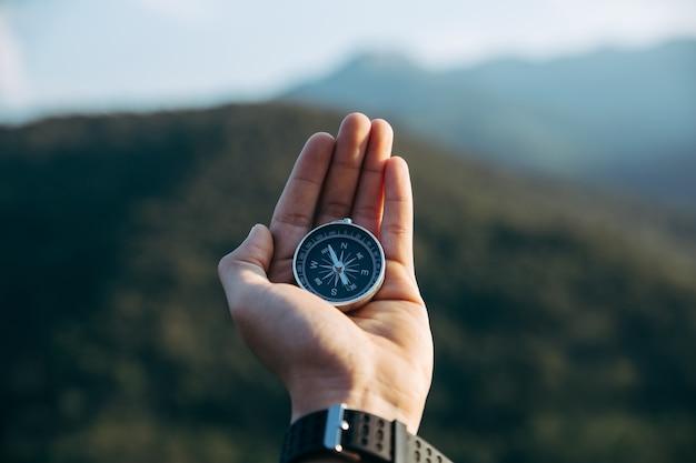 Kompas w rękach podróżnika, na szczycie góry.