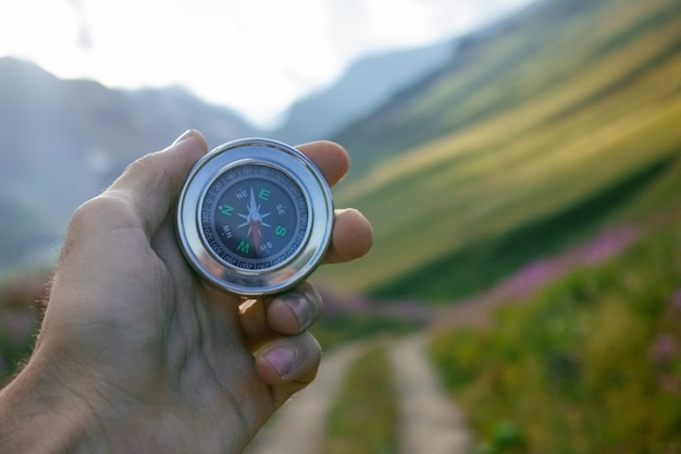 Kompas w ręku na tle przyrody