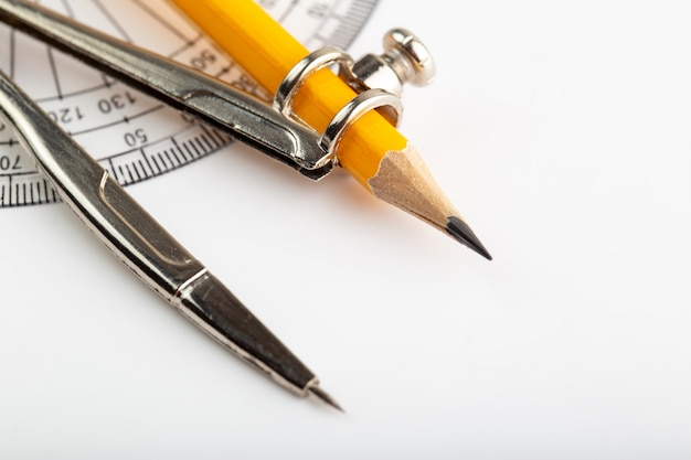 Kompas z bliska ołówkiem do rysowania i szkicowania na białej ścianie