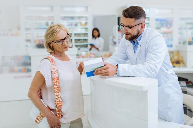 Kompetentny aptekarz. uważna kobieta będąca we wszystkich uszach słuchając przydatnych zaleceń