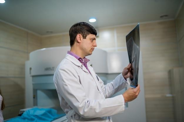 Kompetentny lekarz czytający zdjęcie rentgenowskie w pobliżu maszyny do obrazowania metodą rezonansu magnetycznego.