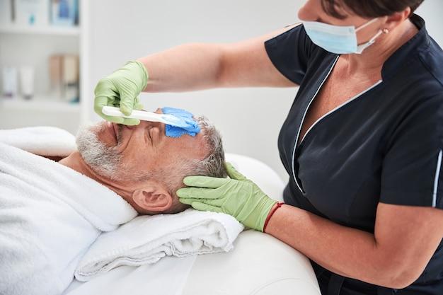 Kompetentny terapeuta spa noszący maskę i trzymający łopatkę podczas nakładania niebieskiego kremu na twarz starszego mężczyzny
