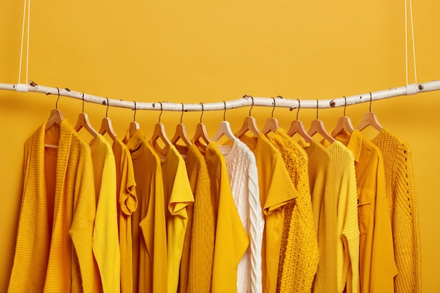 Komplet jasnożółtych ubrań i jednego białego swetra na wieszakach. kolekcja damskich strojów do noszenia. różnorodne stroje na ciepłe i upalne dni.