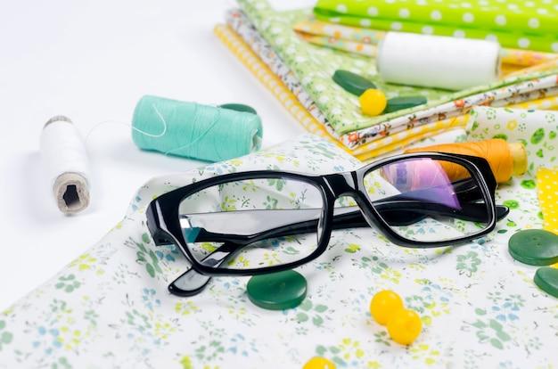 Komplet kolorowych żółto-zielonych materiałów, nożyczki, guziki, szpulki nici