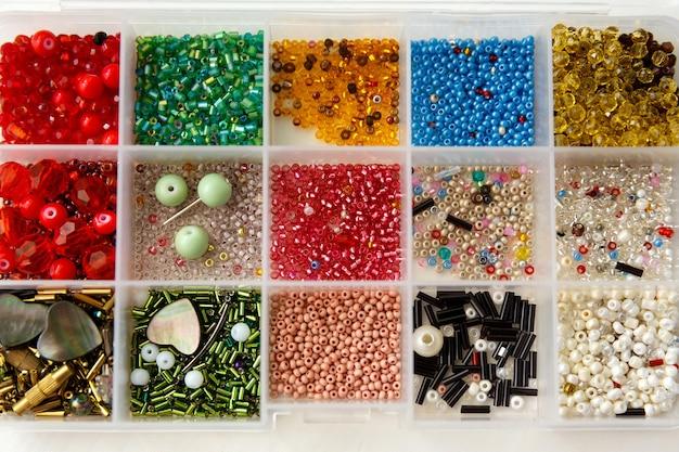 Komplet koralików o różnych kolorach, kształtach, rozmiarach w pojemniku