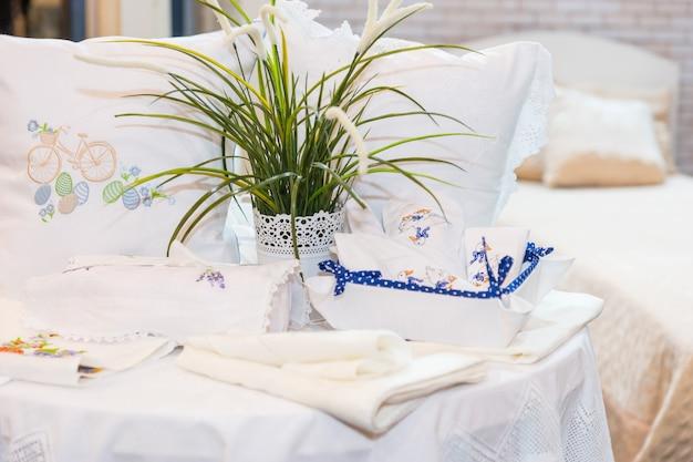 Komplet poduszek ze zgrabnym haftem przy pościeli i zielonej roślince w sklepie agd