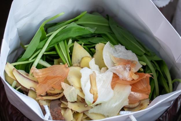 Kompostowanie resztek żywności ekologicznej. kompost w przyjaznej dla środowiska papierowej torbie wykonanej z materiałów pochodzących z recyklingu.