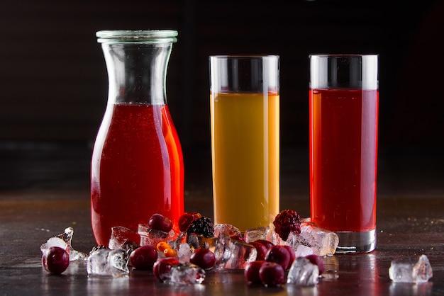 Kompot jagód, owoce w słoiku i szklanki na ciemnym drewnianym stole