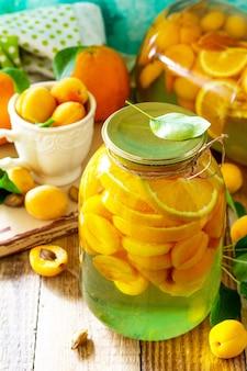 Kompot morelowy i pomarańczowy oraz świeża organiczna pomarańcza morelowa domowa konserwa