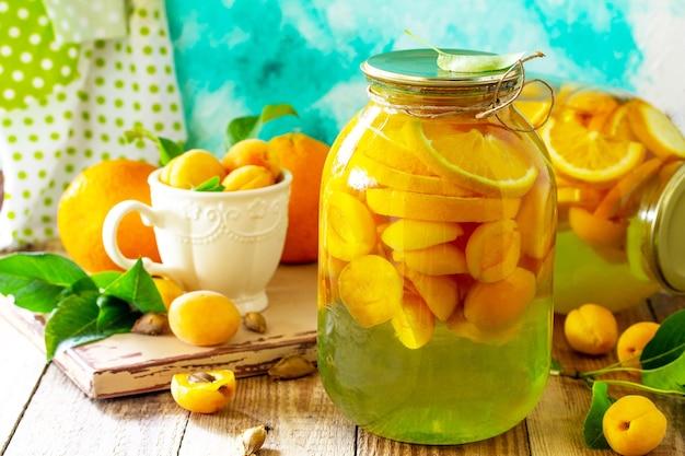 Kompot morelowy i pomarańczowy oraz świeża organiczna pomarańcza morelowa na drewnianym stole w kuchni
