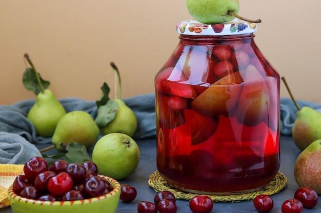 Kompot z gruszek i wiśni w słoiku na stole, zbiór na zimę, poziome zdjęcie