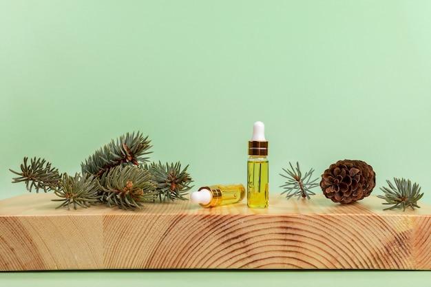 Kompozycja aromaterapeutyczna i spa z olejkiem eterycznym świerkowym w małych szklanych butelkach, zielonych gałązkach i stożku na drewnianym bukszpanu stoją na jasnozielonym tle. skopiuj miejsce na tekst.