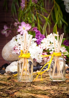 Kompozycja aromaterapeutyczna i wellness z wazonem, kwiatami i patyczkami.