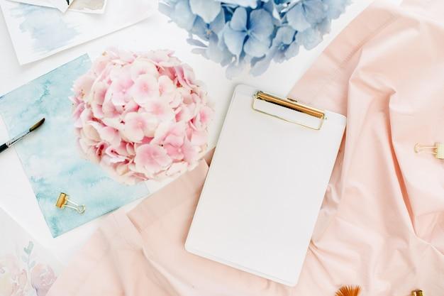 Kompozycja artystyczna biurko do pracy w domu ze schowkiem na kopię, bukiet pastelowych kwiatów hortensji, akwarela, brzoskwiniowy koc