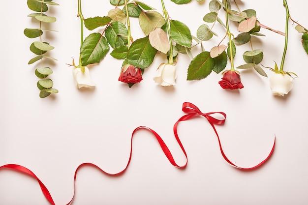 Kompozycja białych i czerwonych róż z czerwoną wstążką