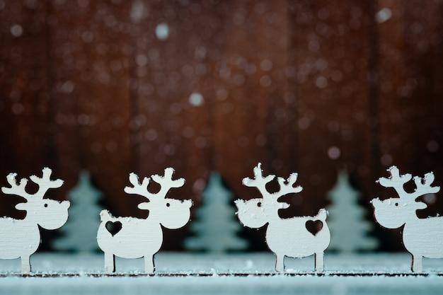 Kompozycja białych reniferów i choinek na drewnianych. świąteczny wystrój