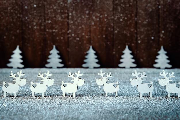 Kompozycja białych reniferów i choinek. świąteczne ozdoby