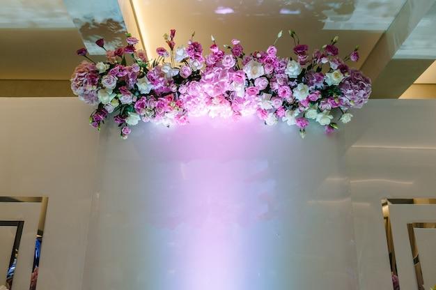 Kompozycja bukietów kwiatów w pastelowych kolorach w strefie zdjęć. przygotowanie ślubu, dekoracja uroczystości. miejsce na tekst.