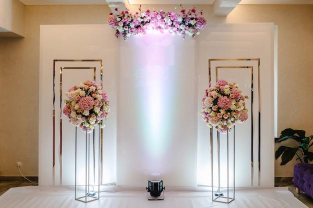 Kompozycja bukietów kwiatów w wazonach w pastelowych kolorach w strefie zdjęć. przygotowanie ślubu, dekoracja uroczystości. miejsce na tekst.