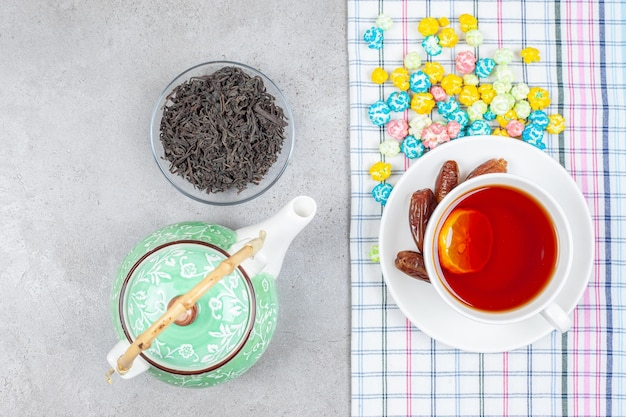 Kompozycja czajnika, miseczki fusów i filiżanki herbaty na ręczniku z rozsypanymi popcornowymi cukierkami na marmurowym tle. wysokiej jakości zdjęcie