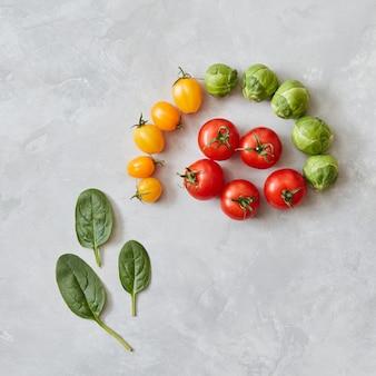 Kompozycja czerwonych i żółtych pomidorów oraz zielonych liści szpinaku