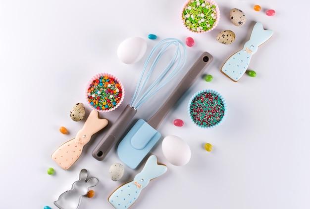 Kompozycja dekoracyjna na wielkanoc. robienie domowych ciasteczek z cukrem. ciastko w kształcie zabawnego królika, narzędzia niezbędne do zrobienia piernika, kolorowe posypki.