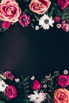 Kompozycja delikatnych letnich kwiatów na czarnym tle widok z góry.