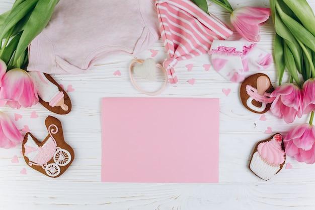 Kompozycja dla noworodków na drewnianym tle z ubrania, różowe tulipany i ciasteczka