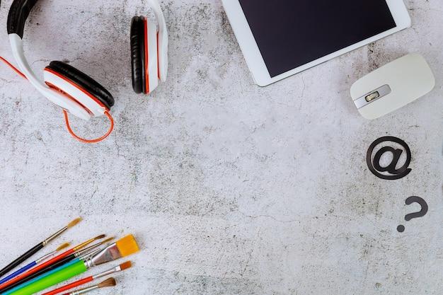Kompozycja do nauki w domu z tabletem, słuchawkami i myszą.