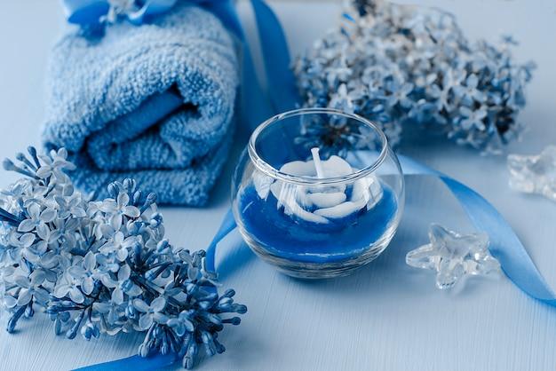 Kompozycja do spa kwiatów, świec i ręczników w klasycznym niebieskim kolorze