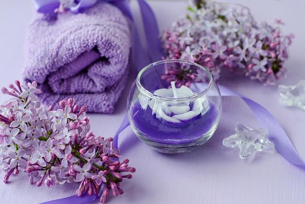 Kompozycja do spa z kwiatów bzu, świec i ręczników