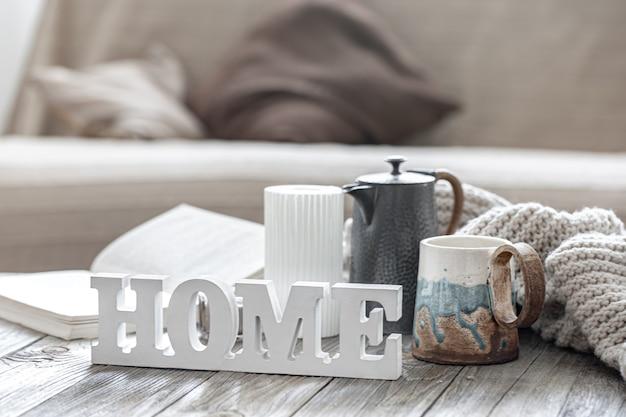Kompozycja domu z ozdobnym napisem home, herbata, dzianina i detale wystroju na rozmytym tle wnętrza pokoju.