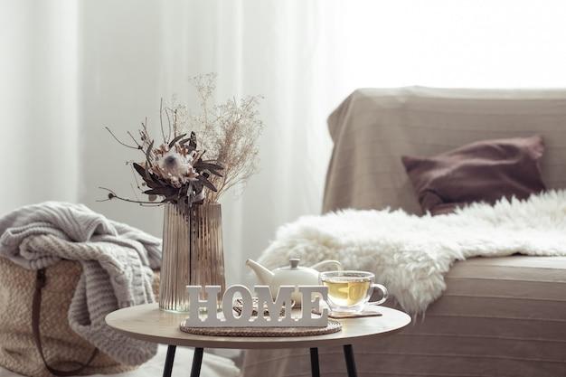 Kompozycja domu z ozdobnym słowem home, herbatą i detalami dekoracyjnymi.