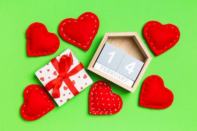 Kompozycja drewnianego kalendarza, białych świątecznych prezentowych pudełek i czerwonych tekstylnych serc