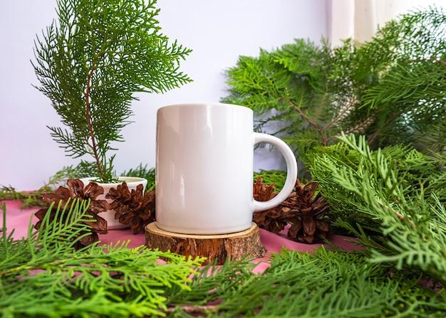 Kompozycja eksponuje produkt. biały kubek na starym okrągłym drewnie z dekoracją z liści jodły. letnie pomysły na wyświetlanie produktów