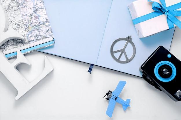 Kompozycja elementów podróży z aparatem fotograficznym, zabawką samolotu, mapą, albumem fotograficznym, symbolem pokoju