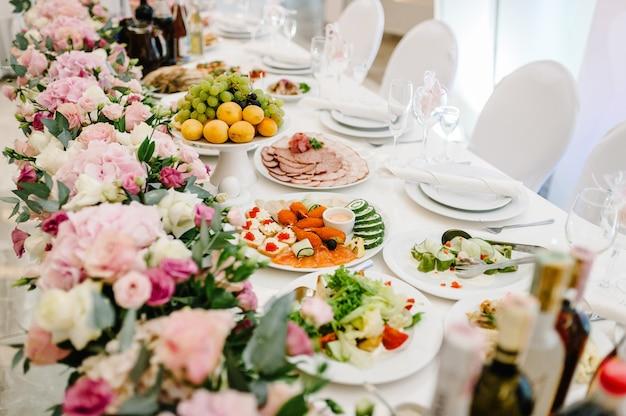 Kompozycja fioletowych, różowych kwiatów i zieleni stojących na serwowanym stole w przestrzeni wesela. stół nowożeńców podawany z naczyniami i sztućcami. ścieśniać.