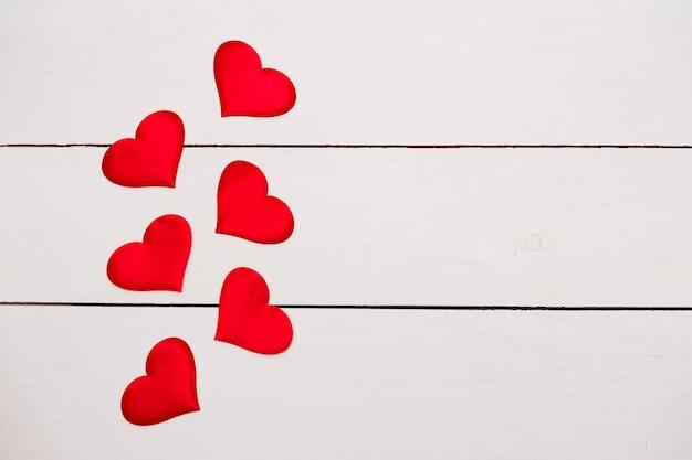 Kompozycja flatlay z sercami na tle drewnianych.