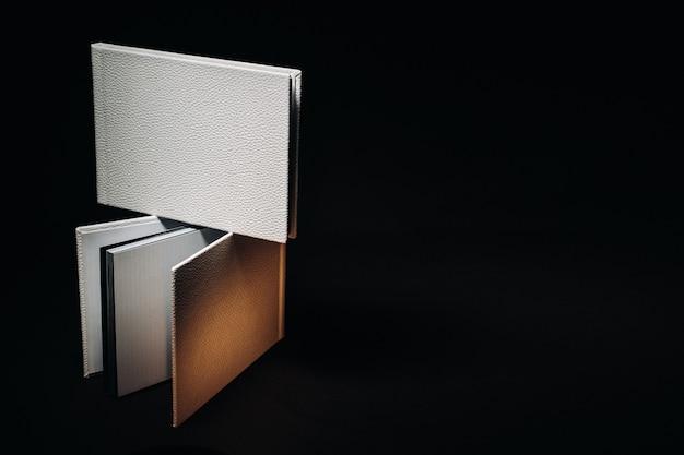Kompozycja fotoksiążek w różnych rozmiarach z naturalnej białej skóry. biała księga na ciemnym tle.