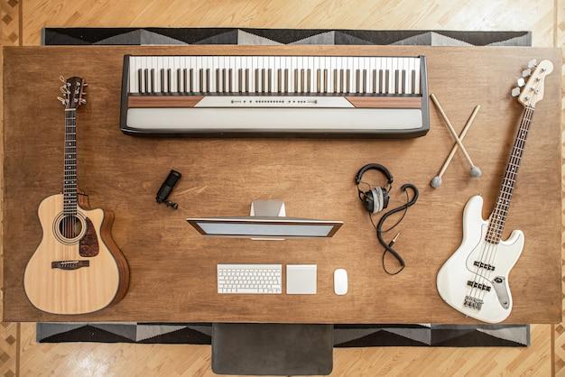 Kompozycja gitary akustycznej, gitary basowej, klawiszy muzycznych, człowieka przy komputerze i słuchawkach oraz półki na bębny na dużym drewnianym stole.