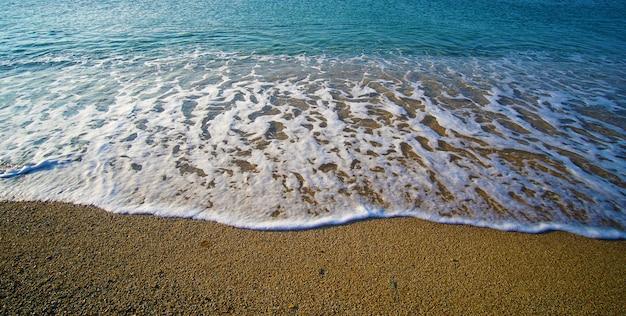 Kompozycja graficzna narysowana przez morze na złotym i niepowtarzalnym piasku plaży lia na mykonos