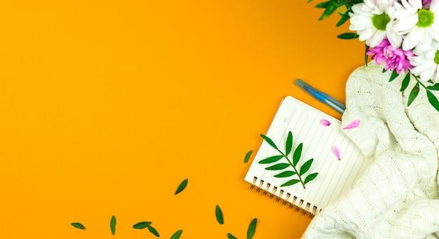 Kompozycja hello spring, tło na wakacje i na świętowanie dnia matki, dzień kobiet, zielone liście i różowe płatki, ciepły sweter i bukiet kwiatów, zdjęcie przestrzeni roboczej