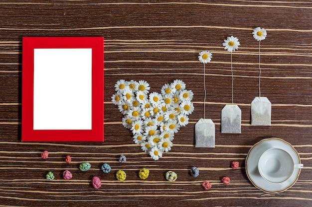 Kompozycja herbaty i kwiatów oryginalna kompozycja herbaty i kwiatów na drewnianym stole