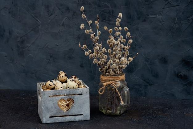 Kompozycja jaj przepiórczych w drewnianym pudełku gałęzi wierzby w wazonie