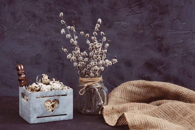 Kompozycja jaj przepiórczych w drewnianym pudełku z czekoladową gałązką wierzby wielkanocnej w wazonie.