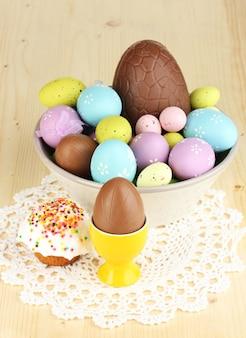 Kompozycja jaj wielkanocnych i czekoladowych oraz simnel na drewnianym stole z bliska
